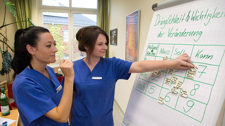 Two nurses looking at a flip chart