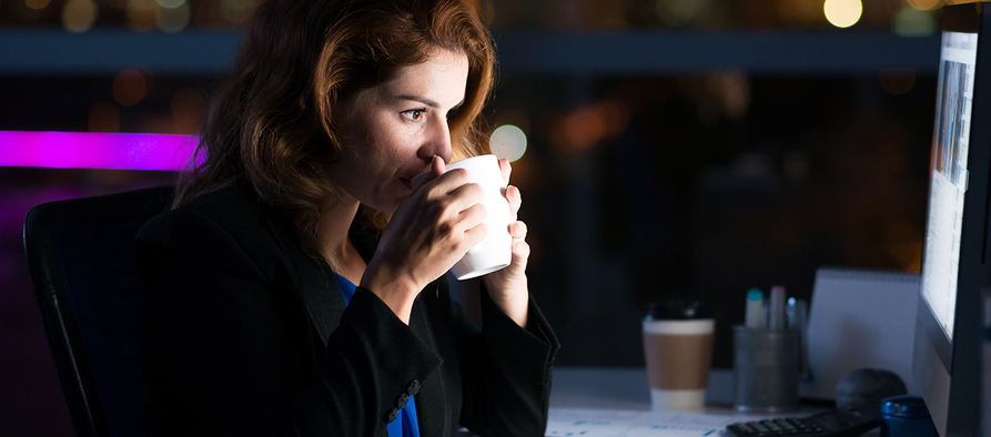 Business woman drinking coffee to get some energy for working overtime