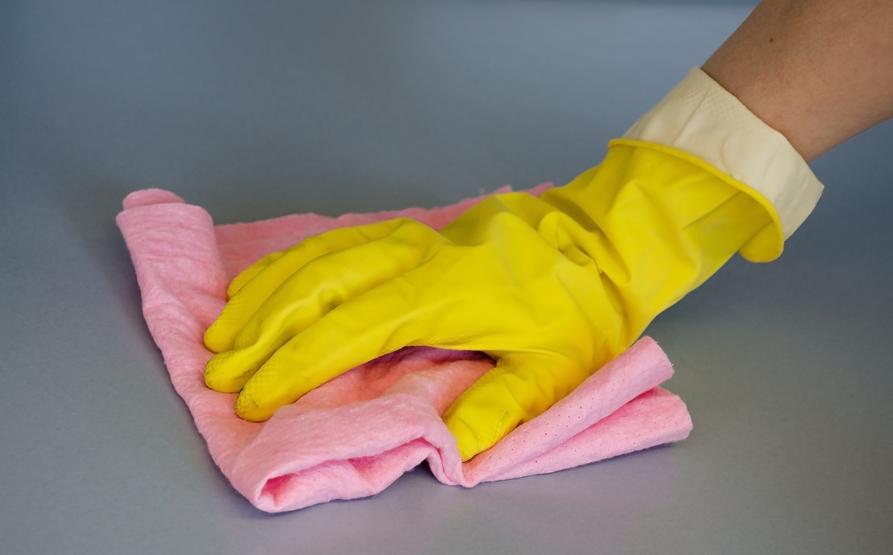 A hand in a yellow protective glove with a turned-up cuff wipes down a grey-blue surface with a pink cloth.
