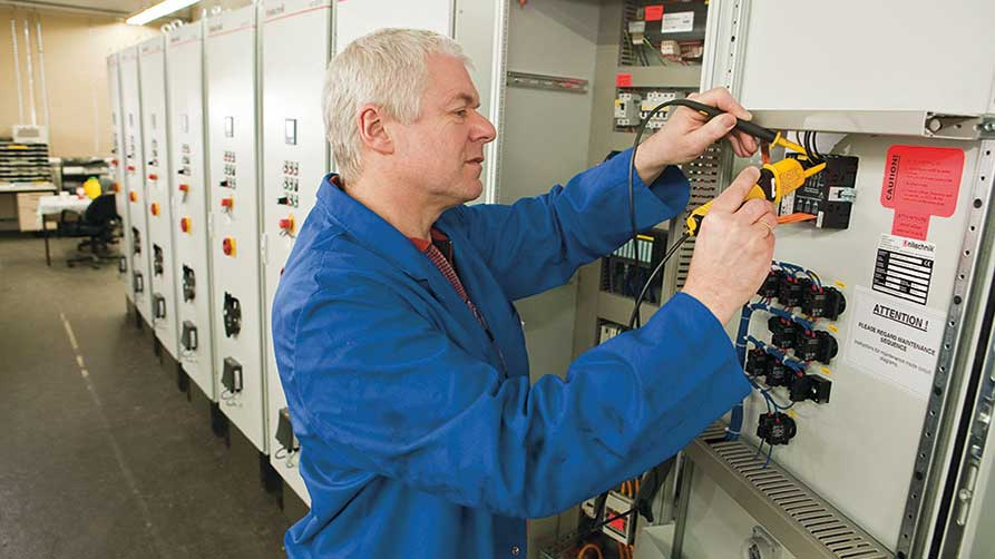 Electrician during test work on a control cabinet