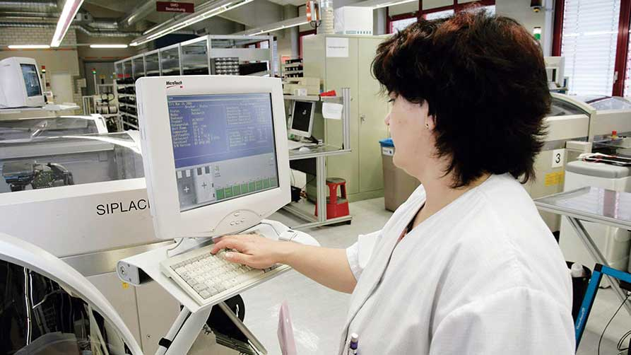 Woman with white work coat in front of a VDU workstation